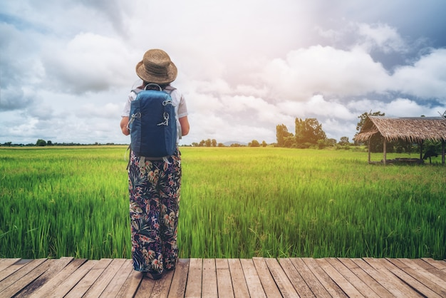 アジアの田んぼの風景をハイキングする女性旅行者。