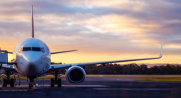 タスマニア州の日没時の空港滑走路に飛行機