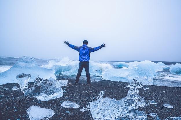 アイスランドのダイヤモンドビーチの男性旅行者。
