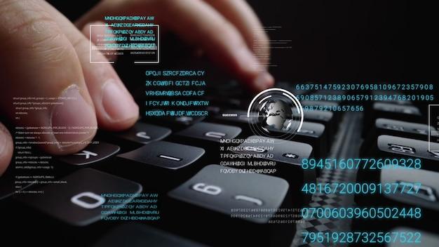 グラフィックユーザーインターフェイスを備えたラップトップコンピューターのキーボードで作業する人
