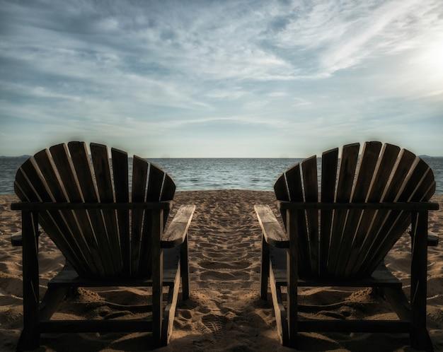 太陽が降り注ぐビーチのカップルの椅子。ハイコントラストの夏のトーン。