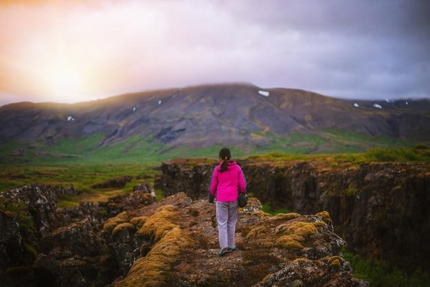 アイスランドの風景全体をハイキングする女性旅行者。
