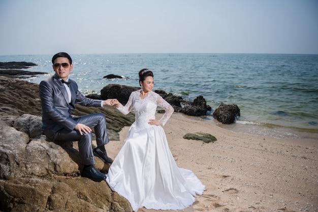 ビーチの結婚式のためのウェディングドレスとスーツを着ているアジアカップル。ビーチのコンセプトをカップルします。白いブライダルドレス。