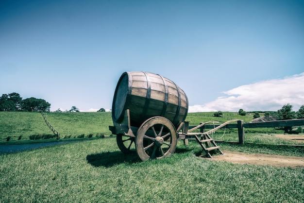 ビンテージトーンの緑の芝生フィールドでワイン樽