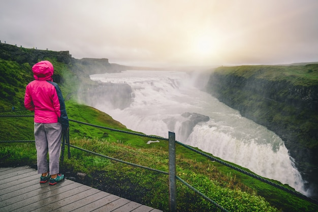 Путешественник путешествует к водопаду гульфосс в исландии.
