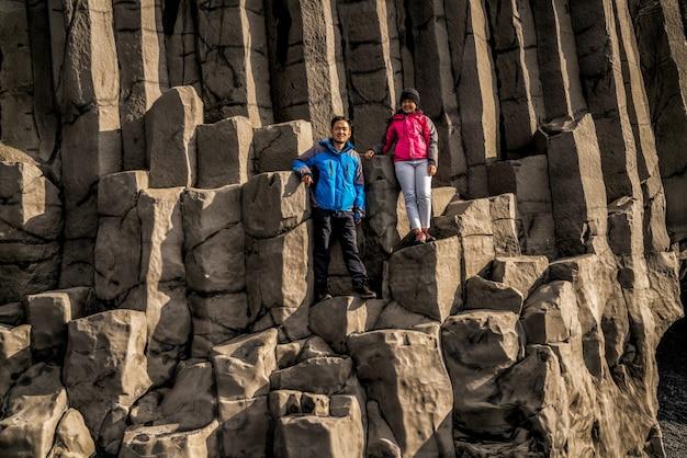 ヴィック、アイスランドの六角形の岩の上の旅行者。