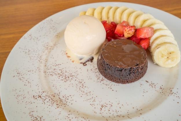 バニラアイスクリーム、ストロベリー、バナナのトッピングが入ったチョコレート溶岩ケーキ