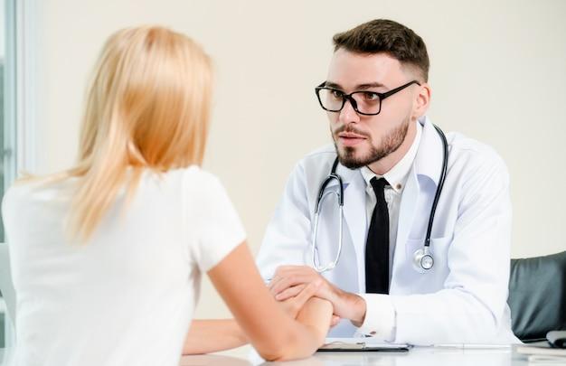男性の医者は、患者の手を持って病院にいる女性患者を癒す。