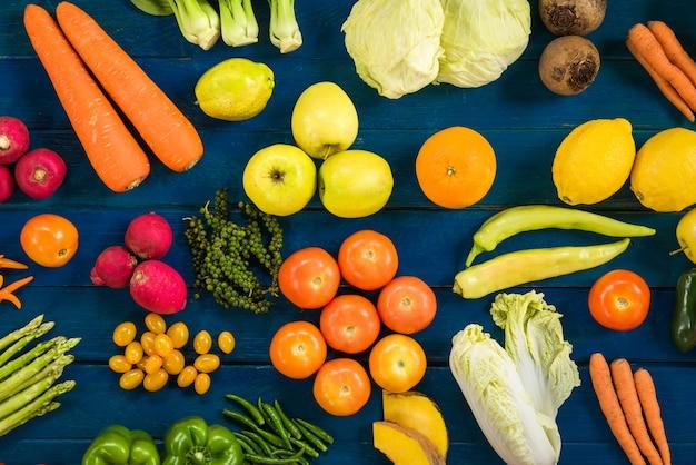 新鮮な果物や野菜のフラットなレイアウトは、健康的な食事のための異なる果物や野菜、青い板張りの背景に色とりどりの果物や野菜