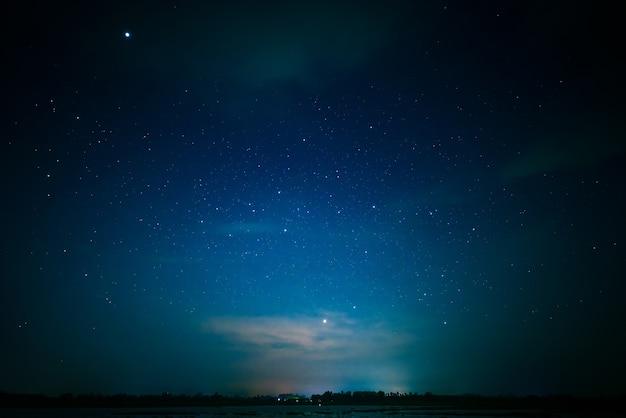 Синяя и темная ночь с яркими многими звездами над озером