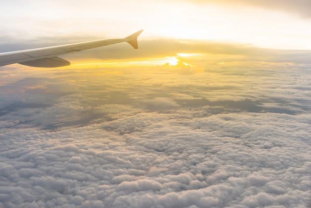 飛行機の窓から見た美しい日光と曇り