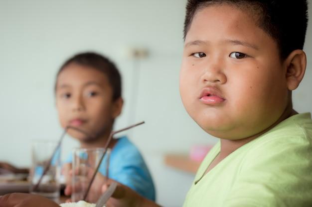 Азиатские дети мальчик, едят здоровую пищу в столовой или столовой.