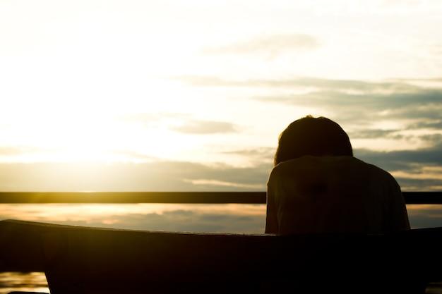 美しい夕日の背景の上に椅子に座っている女性のシルエット。
