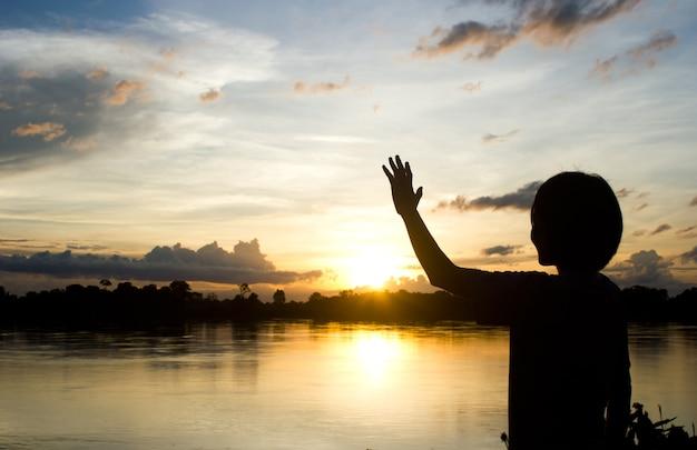 シルエット女性は美しい太陽を背景に彼女の手を示す背景を設定