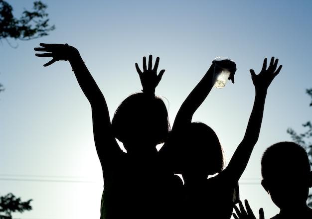シルエット、夕暮れの背景で遊んでいる幸せな子供のグループ。