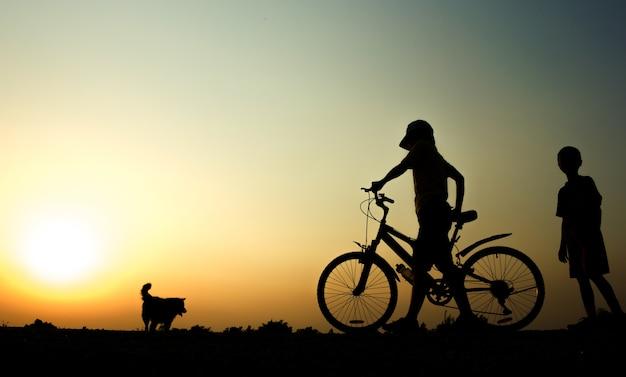 Мальчик и женщина фитнес-силуэт восход на велосипеде тренировки оздоровительный концепции.