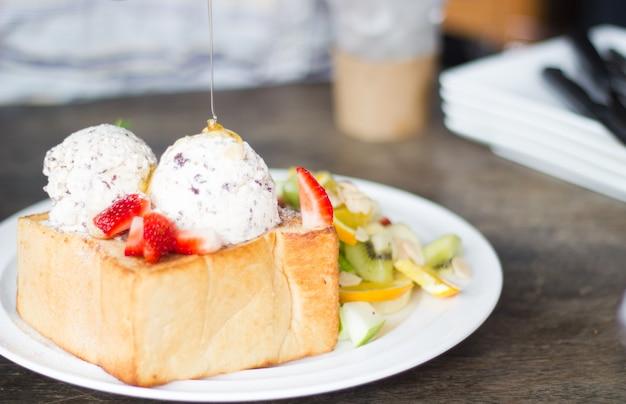 果物と蜂蜜のトーストと貧弱な照明のアイスクリームの選択的な焦点。
