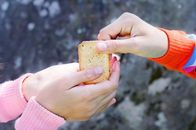 食べ物を分かち合う。小さな子供にクラッカーを与える女性。チャリティーコンセプト。