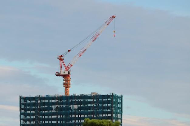 夕暮れの青い空に対して緑色の覆いをする建物の建設用クレーン