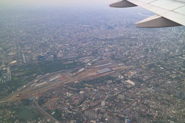 Вид с воздуха на бангкок, таиланд со зданием в большом городе и крылом самолета.