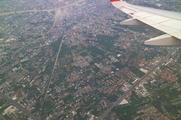 С высоты птичьего полета бангкок, таиланд со зданием в большом городе, реке и крыле самолета.