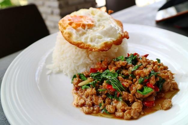 バジルの葉と白い皿に目玉焼きのピリ辛揚げ豚肉とご飯。タイ風料理。食品のコンセプト