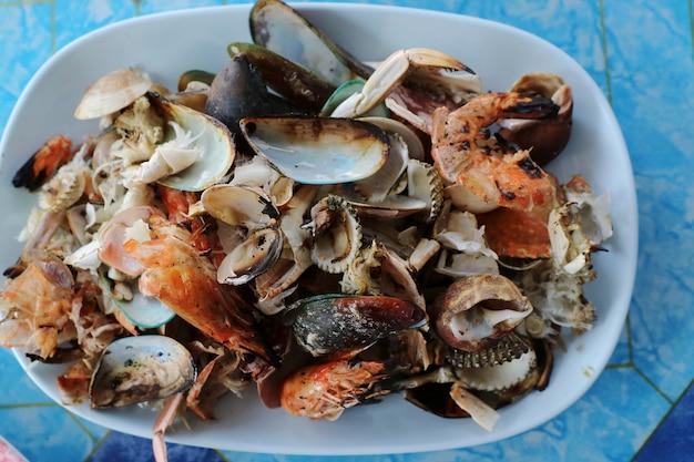 Раковины, раковины креветок и раков крабов на белой плите в ресторане морепродуктов.