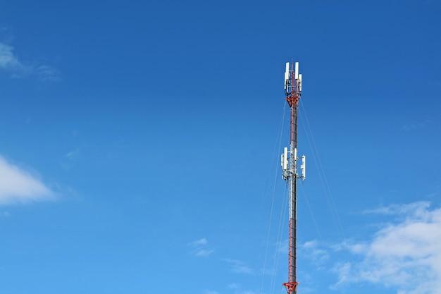 Здание башни антенны с голубым, оранжевым небом и белым облаком.