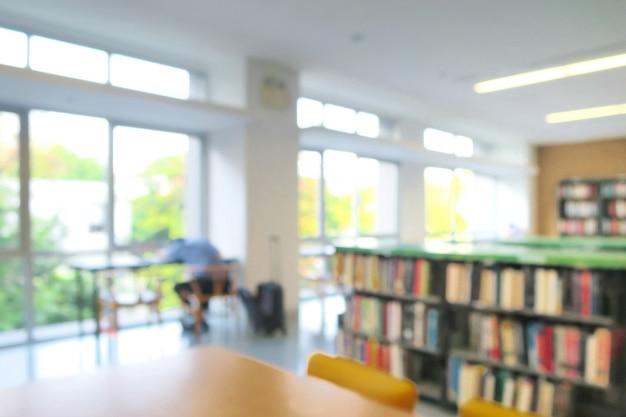 本棚の中の本と図書館のインテリアのぼやけ。男子学生が昼寝をする。