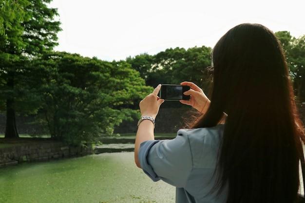 アジアの長い髪の女性の背面図は、夏には緑豊かな公園で携帯電話で写真を撮る。