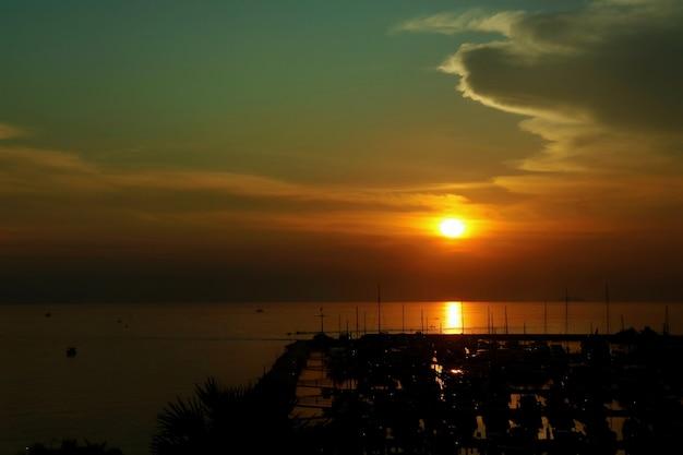 ヨットマリーナで大きな群れと夕日。低キー。自然と交通機関のコンセプト。