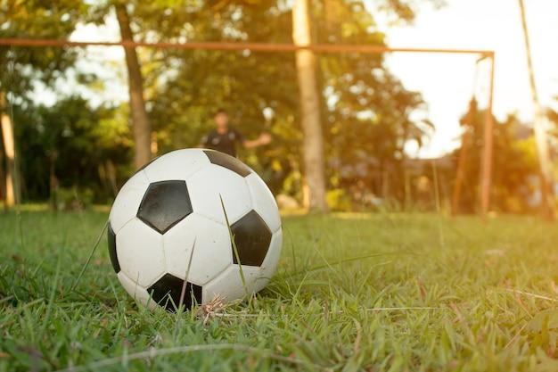 スポーツフィールドでサッカーボールを蹴っている少年。子供のためのサッカーサッカートレーニングセッション。