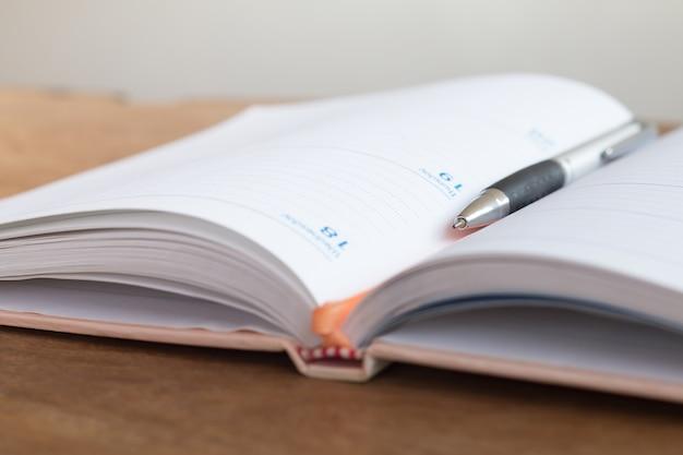 主催者の本を持つペンのソフトフォーカス。