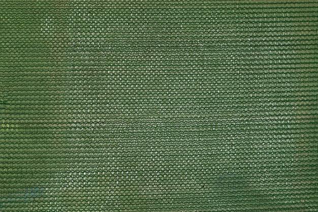緑の背景のための抽象的なプラスチックのネットテクスチャ