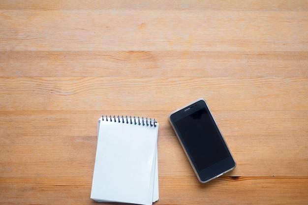 スマートフォンと整理の作業テーブル、オフィスデスクの背景の概念