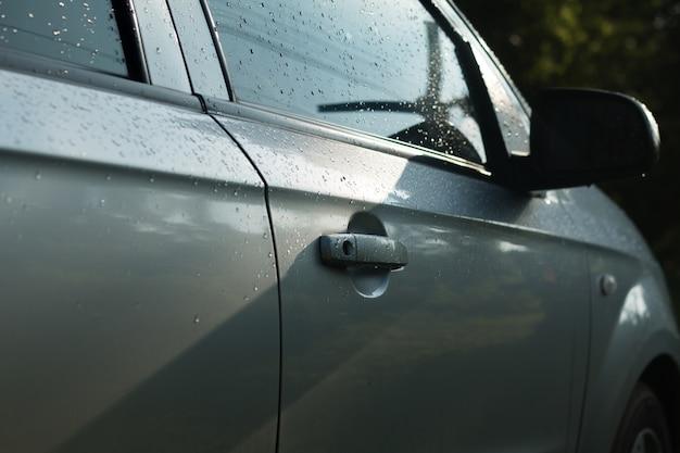 貧弱な照明のシーンで雨が降った後ドアの車のウェットハンドルを閉じます。車のドアのハンドルに水滴