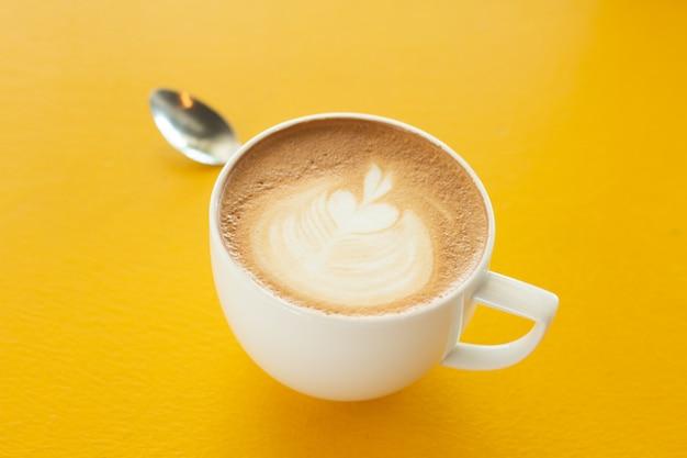 黄色の木製のテーブルの上にホットラテアートコーヒーのカップをクローズアップ