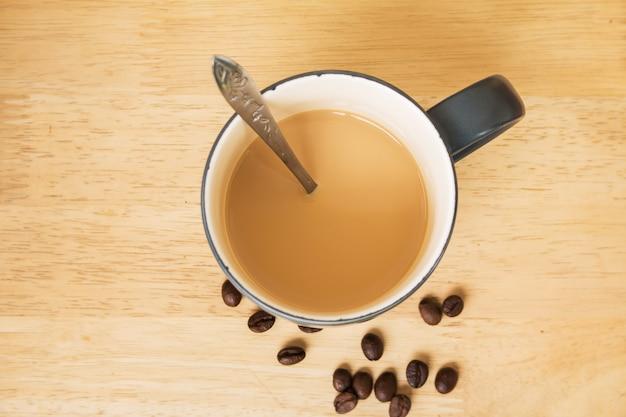 テーブルにミルクとコーヒー豆とコーヒーのカップ