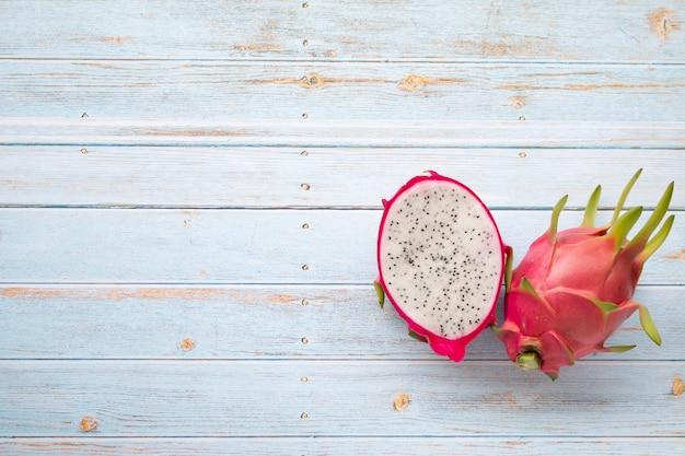 ドラゴンフルーツまたは水色の木製テーブル背景、夏のフルーツのピタヤフルーツ