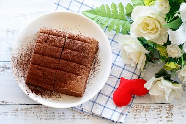 木製のテーブルに置かれた赤いハートの白いプレートに自家製チョコレートブラウニーを閉じる