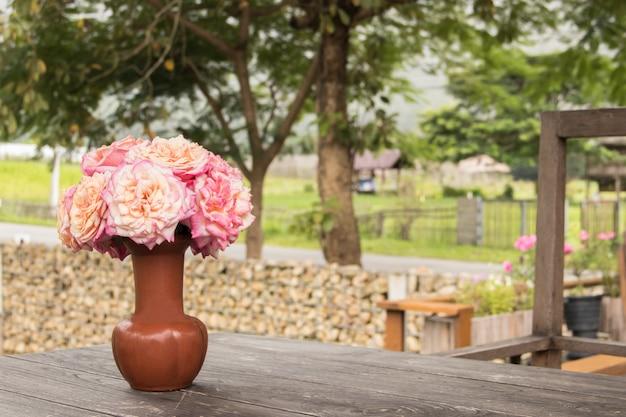 古いテーブル、ぼやけて自然の背景の上の茶色の花瓶に美しいピンクのバラ