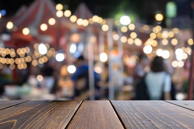 カラフルな背景の前に茶色の空の木製テーブル