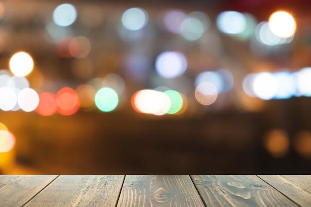 プレゼンテーションとテンプレート製品の前面の木製テーブルぼやけてカラフルなボケ味の背景