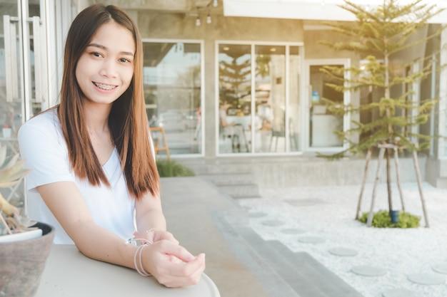 Женщина сидит на стуле, глядя на камеру и улыбается - портрет красивой женщины азии