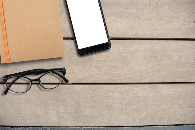 空のモバイル画面と机、上面図、コピースペース、ビジネス、フリーランスの背景概念に茶色と眼鏡の本