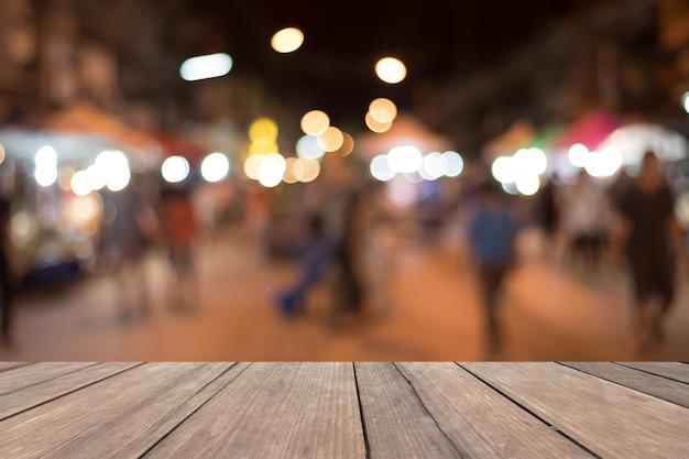 ぼやけている通りの背景に存在するための空の木製テーブル