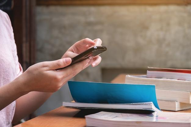 女性が机の上の携帯電話を使用