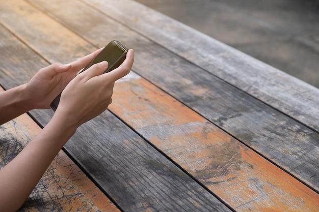Женщина с помощью мобильного телефона на деревянных досках
