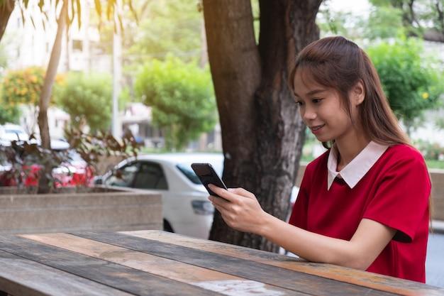 屋外のテーブルで携帯電話を使用して女性