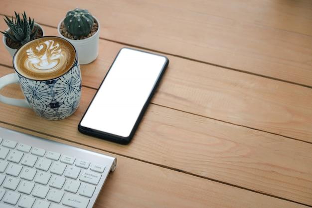 携帯電話の画面と木製のテーブルのワイヤレスキーボードの横にあるホットアートカプチーノコーヒー